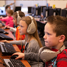 Shadow Valley students wearing headphones and working on computers.